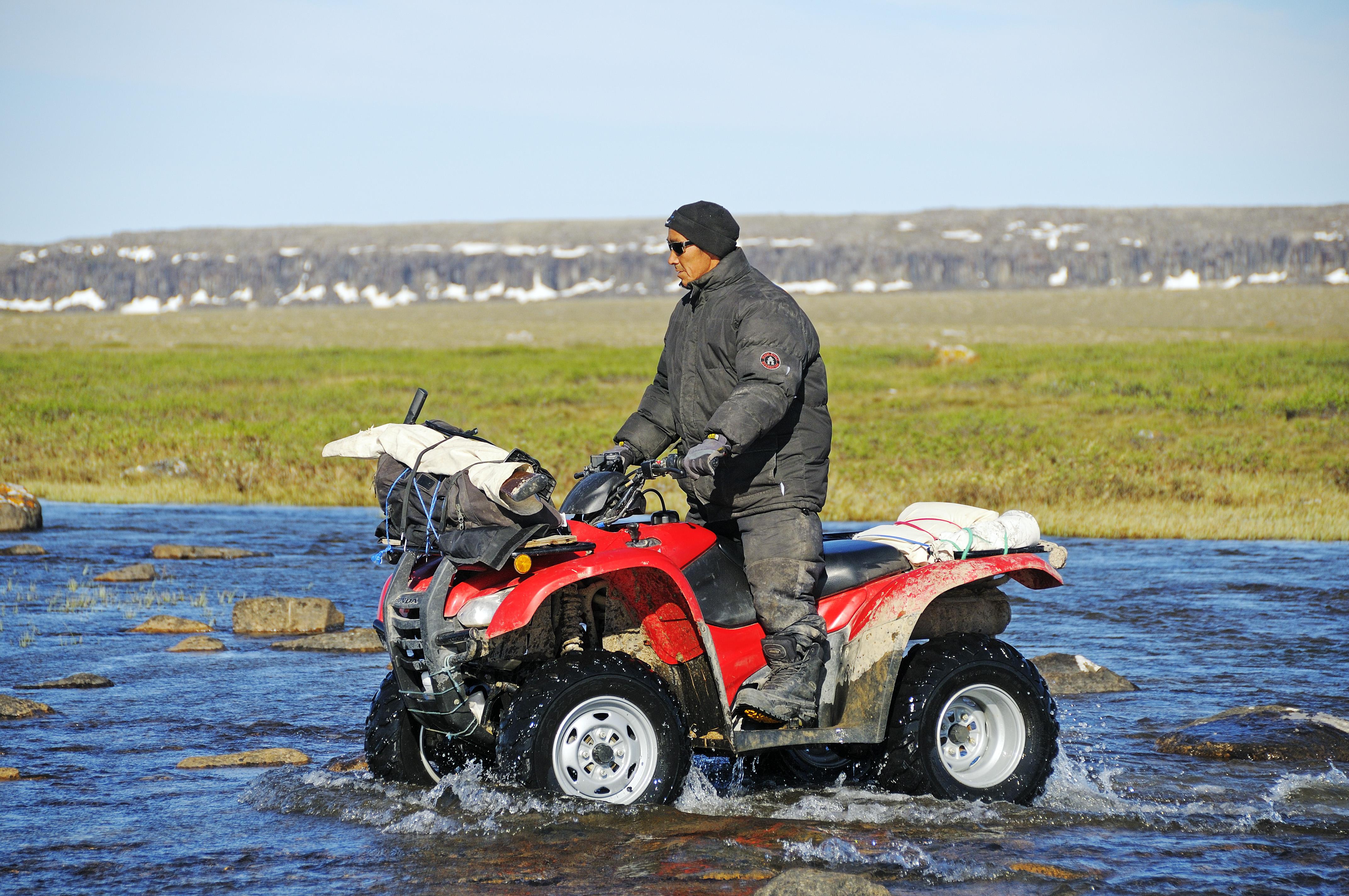 Mann vom Volk der Inuit fährt mit einem Quad (ATV) durch einen Fluss in der Tundra auf Victoria Island (vorher Holman Island), Dorf Ulukhaktok, Northwest Territories, Kanada, Amerika