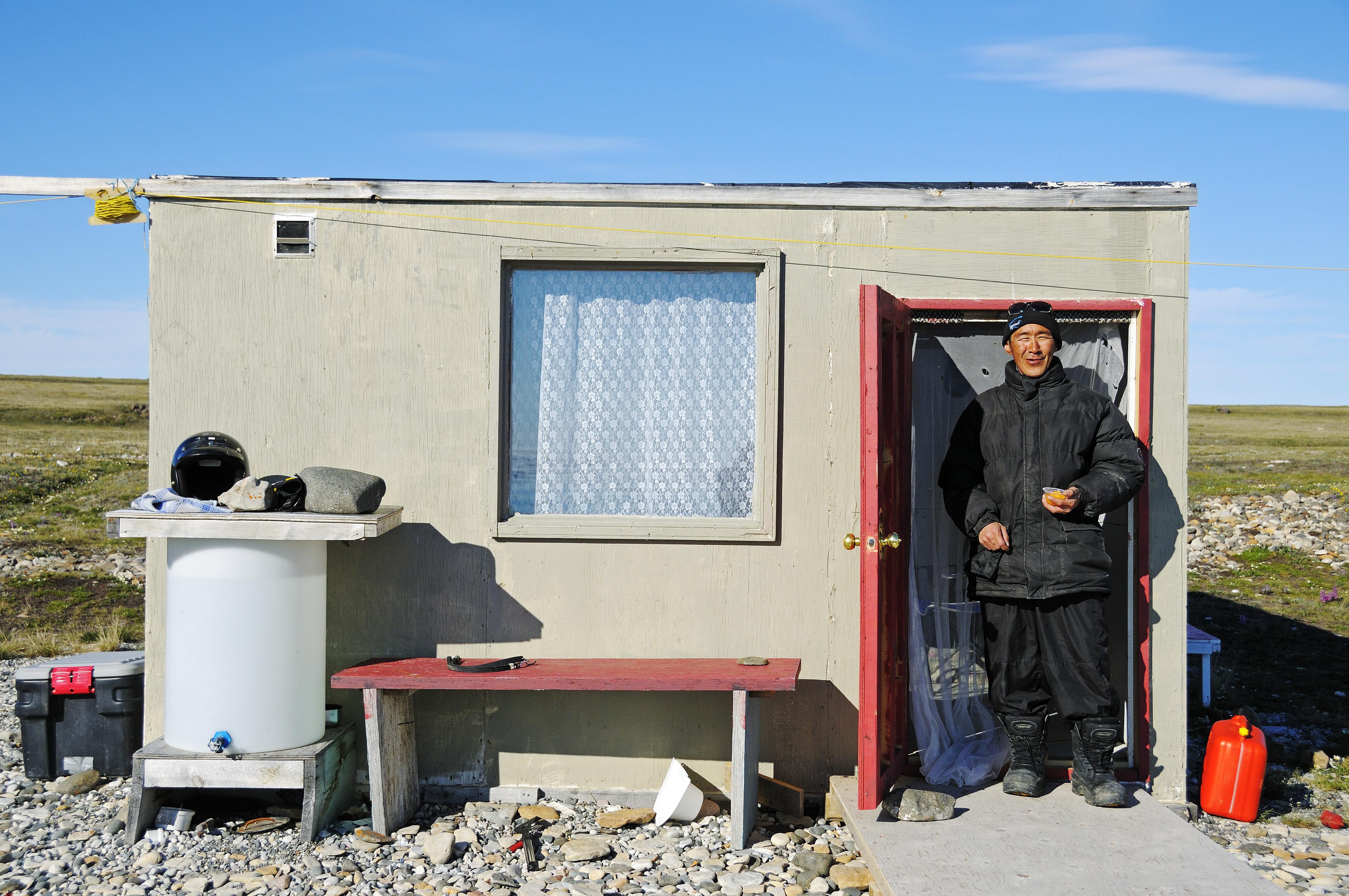 Mann vom Volk der Inuit vor seiner Angel-Hütte am Ufer der Beaufort Sea, Nordpolarmeer, Victoria Island (vorher Holman Island), Dorf Ulukhaktok, Northwest Territories, Kanada, Amerika