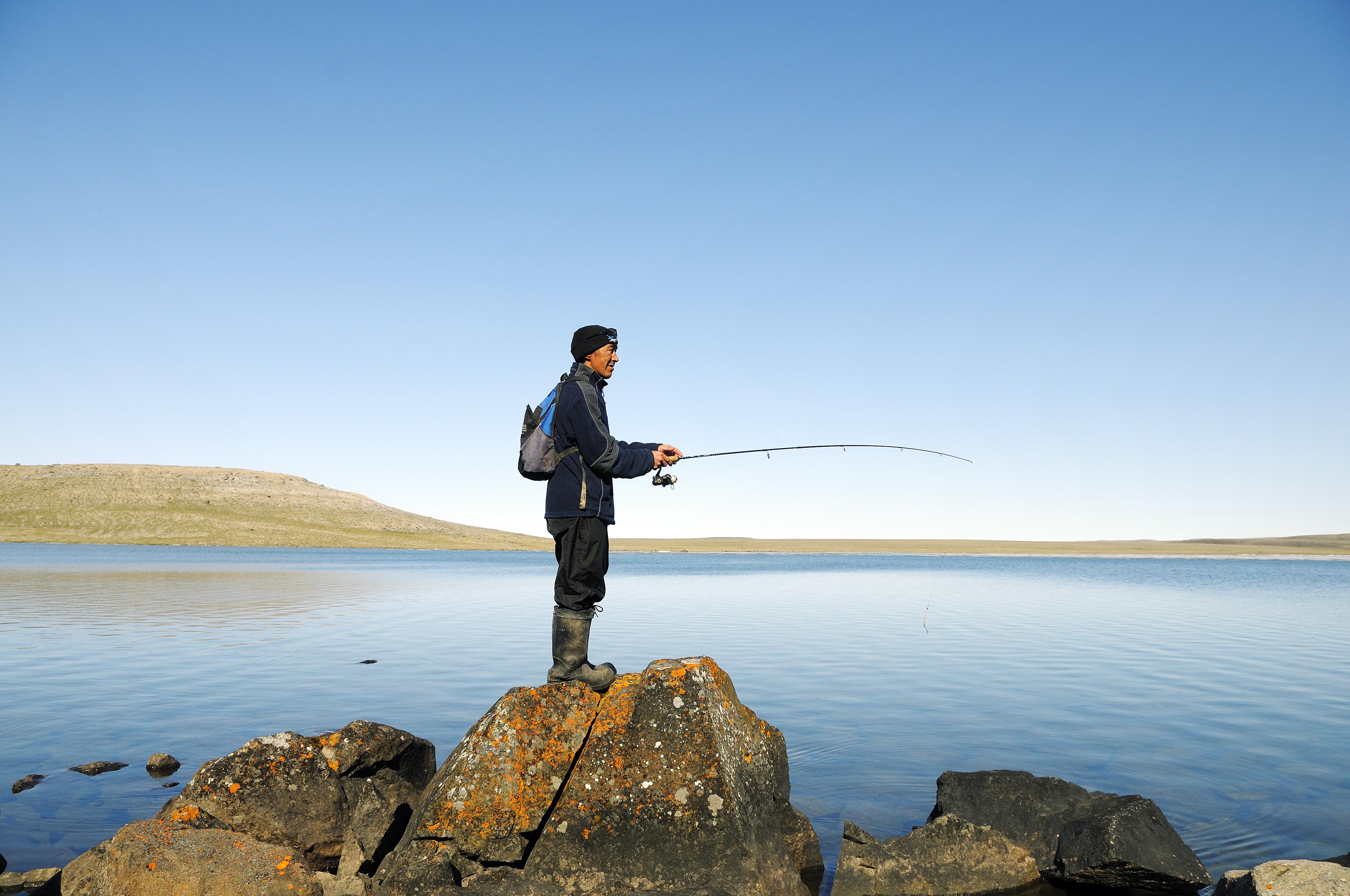 Mann vom Volk der Inuit angelt in einem See, Victoria Island (vorher Holman Island), Dorf Ulukhaktok, Northwest Territories, Kanada, Amerika