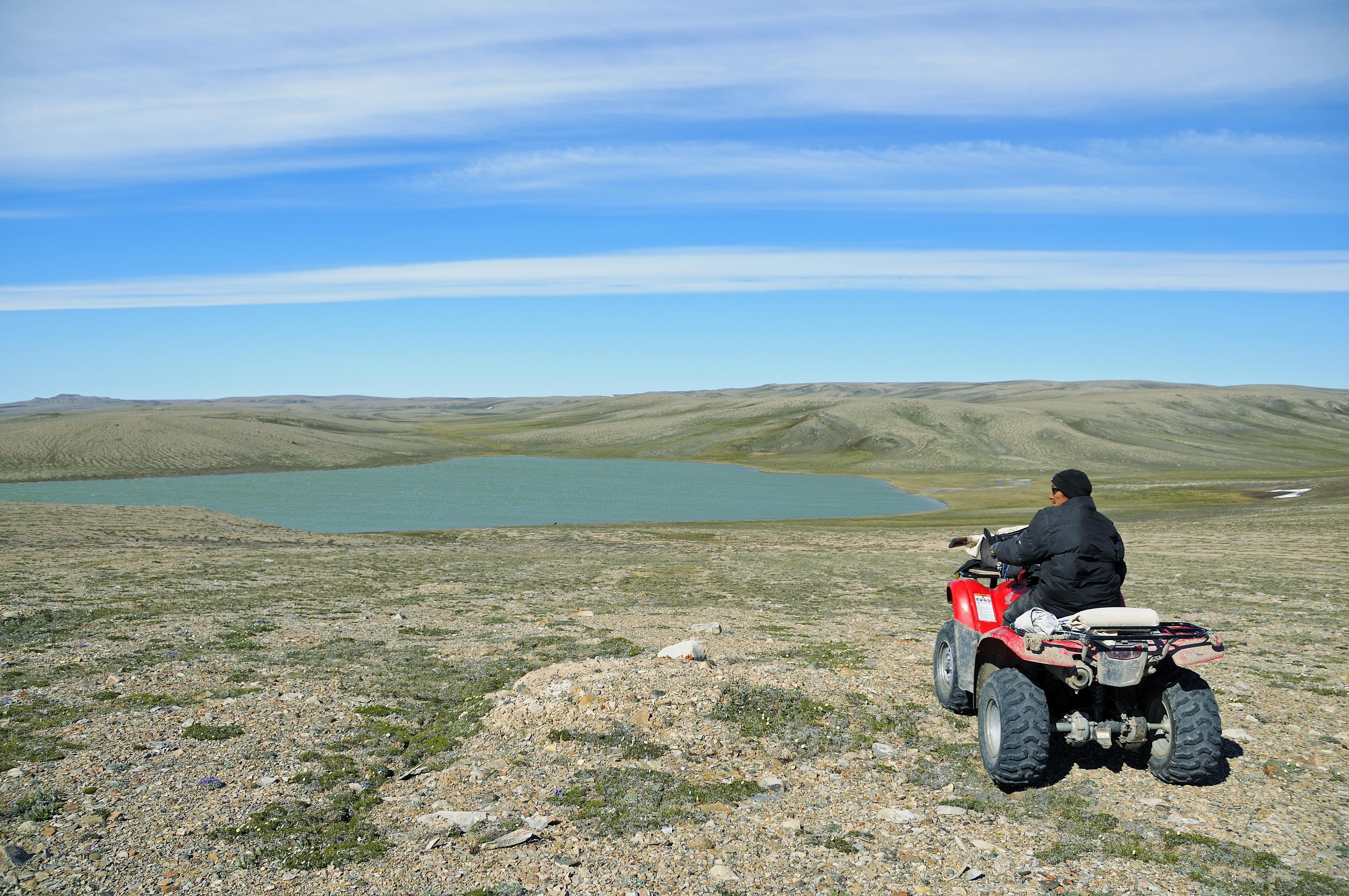 Mann vom Volk der Inuit mit einem Quad (ATM) steht am Ufer eines See in der Tundra, Victoria Island (vorher Holman Island), Dorf Ulukhaktok, Northwest Territories, Kanada, Amerika